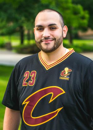 Mike Greco, a male staff member, posing outside on the YSU campus wearing a Cleveland Cavaliers jersey