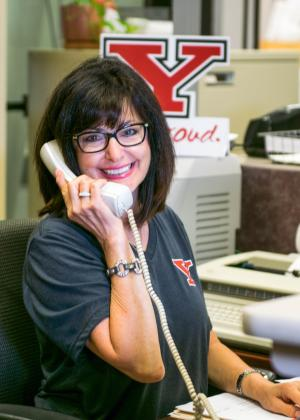 Noreen Yazvac, posing in the office speaking on the phone, wearing a YSU t-shirt that is black and has a Y and Proud sign placed behind her