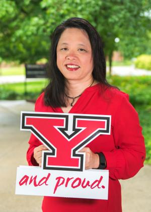 Sue Sracic posing in a red shirt outside on the campus of Youngstown State University holding a Y and Proud sign