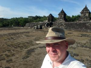 A self-taken photograph of a smiling wear wearing a hat and posing in front of ancient ruins