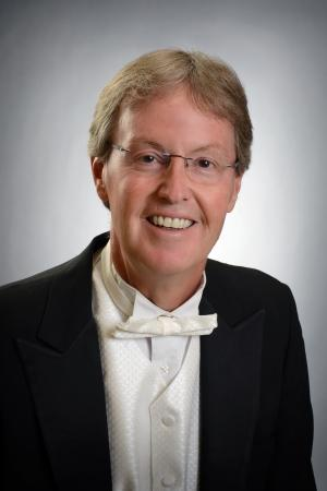 A headshot of a smiling businessman wearing a suit and bowtie and glasses
