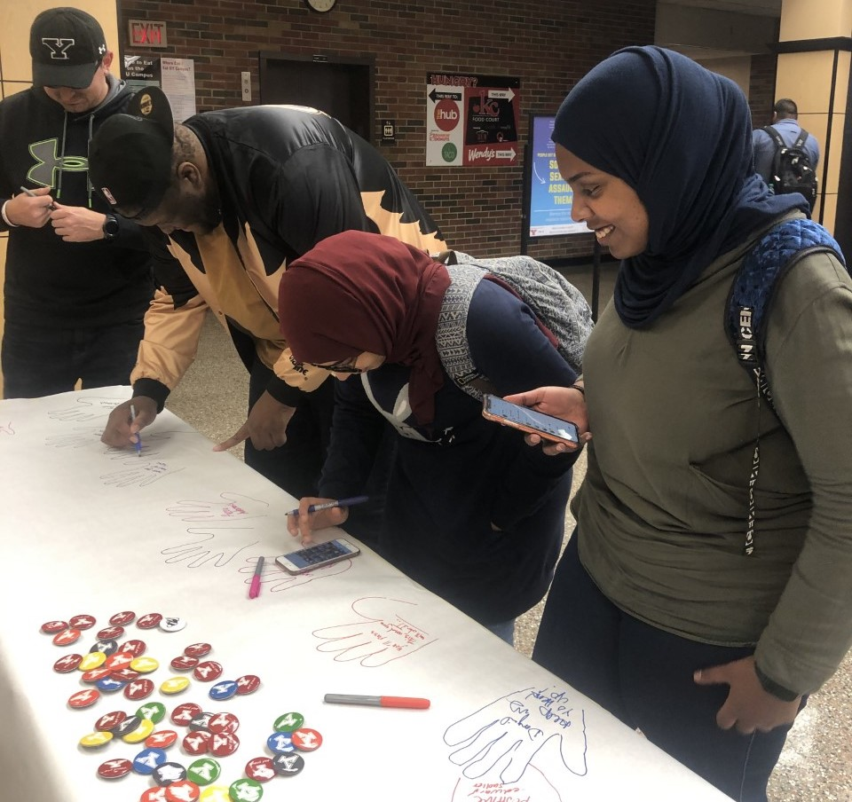 two boys and two girls writing text on a table at the non-violence event